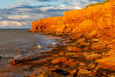 Sunset casts an orange glow on the cliffs near Orby Head, Prince Edward Island National Park