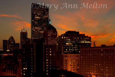 A composite image of  evening Boston cityscape with a sunset sky