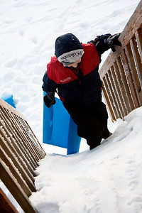 Jake, climbing back up his own snow slide...the deck stairs.