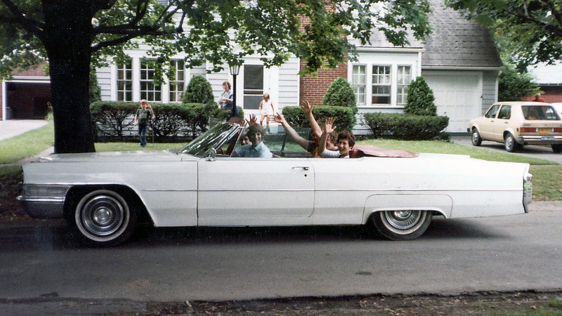 "July 1984:  Eighteen year old Todd is on top of the world behind the wheel of his first car, a 1965 Cadillac Deville convertible.  I took my brother and a few friends for a short drive around the block.  Truth be told, I couldn't go any further than around the block due to things like a coolant leak, bad brakes, and lots of electrical gremlins, (my window is up because it wouldn't go down).  My first car was more ""project"" than actual transportation.  But the convertible top worked which was all that mattered to me."