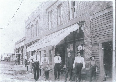 The Zion Street shops were east of the railroad tracks, just north of Catawba Avenue. These men are standing in front of Alex Little's hardware store. Pictured left to right: 1. Caldwell Fidler (born 1880)2. J.C. Westmoreland (born 1884)3. Bob Readling (born 1880)4. ?5. Alex Little6. Mazon WestmorelandAlex Little was mayor of Cornelius in 1913 and 1914.It is rumored that 4 brothers from Denver NC (the Little brothers) married 4 sisters named McCall. It is also rumored that Alex Little left Cornelius & opened Little Hardware in Charlotte. What is the true story?