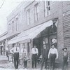 The Zion Street shops were east of the railroad tracks, just north of Catawba Avenue. These men are standing in front of Alex Little's hardware store. Pictured left to right: <br>1. Caldwell Fidler (born 1880)<br>2. J.C. Westmoreland (born 1884)<br>3. Bob Readling (born 1880)<br>4. ?<br>5. Alex Little<br>6. Mazon Westmoreland<br><br>Alex Little was mayor of Cornelius in 1913 and 1914.<br><br>It is rumored that 4 brothers from Denver NC (the Little brothers) married 4 sisters named McCall. It is also rumored that Alex Little left Cornelius & opened Little Hardware in Charlotte. What is the true story?