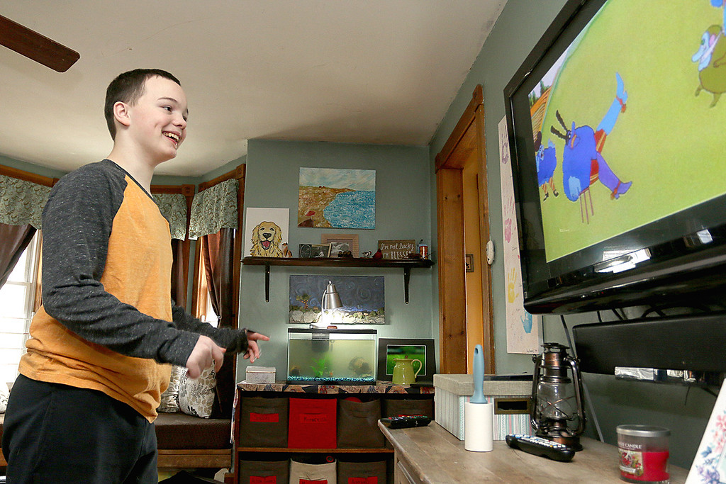 ". Stephanie Hoefsmit and her twin sons, who have autism, are losing their service dog Baker, a golden retriever, because he has cancer. Baker has been very instrumental  in helping her sons cope with the world. Seth Hoefsmit, 14, dances to the movie ""Yellow Submarine\"" in their home on Saturday. SENTINEL & ENTERPRISE/JOHN LOVE"