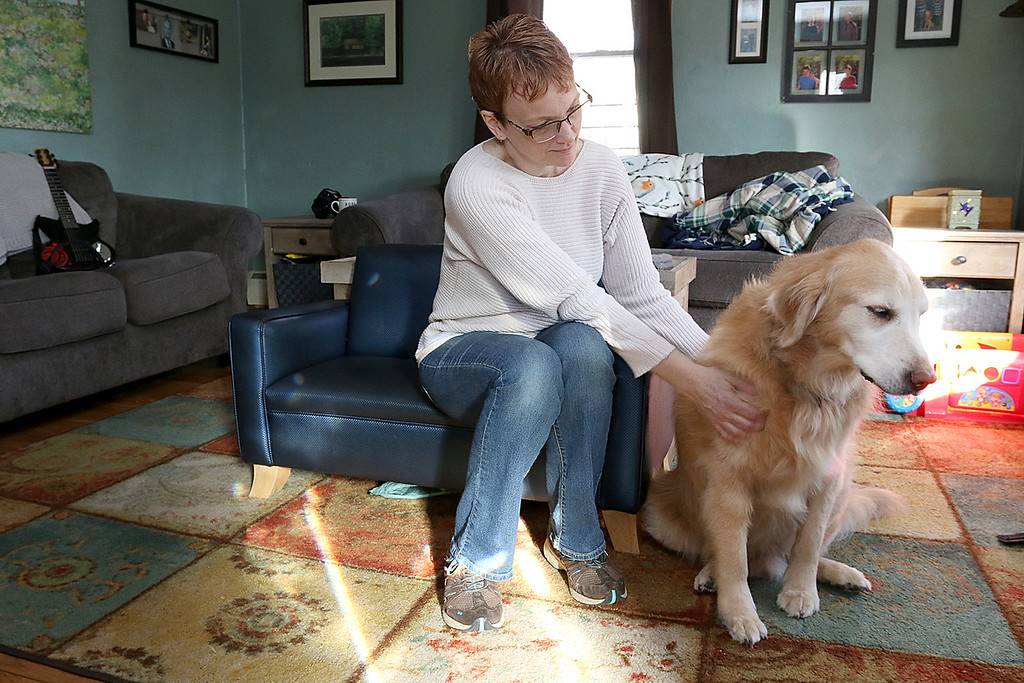 . Stephanie Hoefsmit and her twin sons, who have autism, are losing their service dog Baker, a golden retriever, because he has cancer. Baker has been very instrumental  in helping her sons cope with the world. Stephanie pets Baker in their home on Saturday. SENTINEL & ENTERPRISE/JOHN LOVE