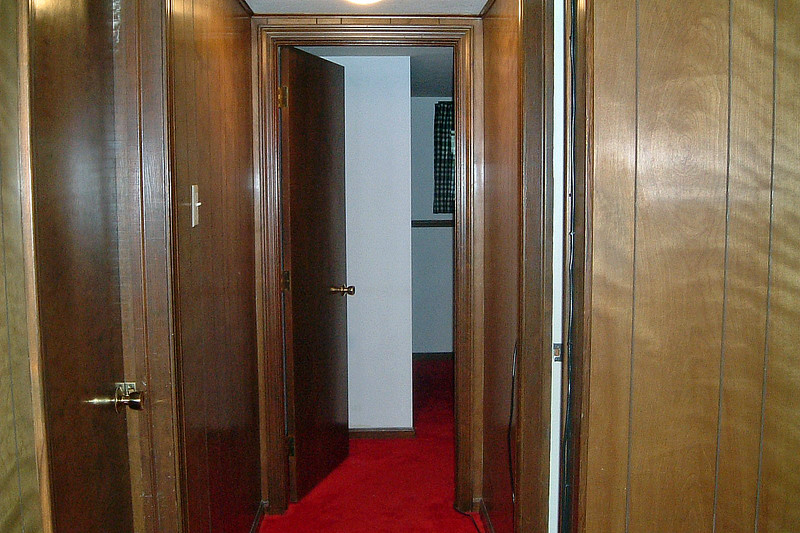 The hallway leads to the bathroom and third bedroom.