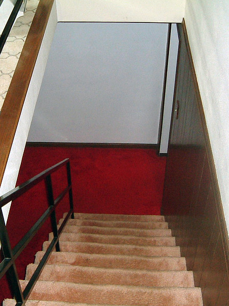 The stairs next to the kitchen lead to the basement.