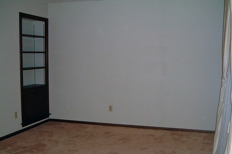 The living room featured a built-in bookshelf in the corner.