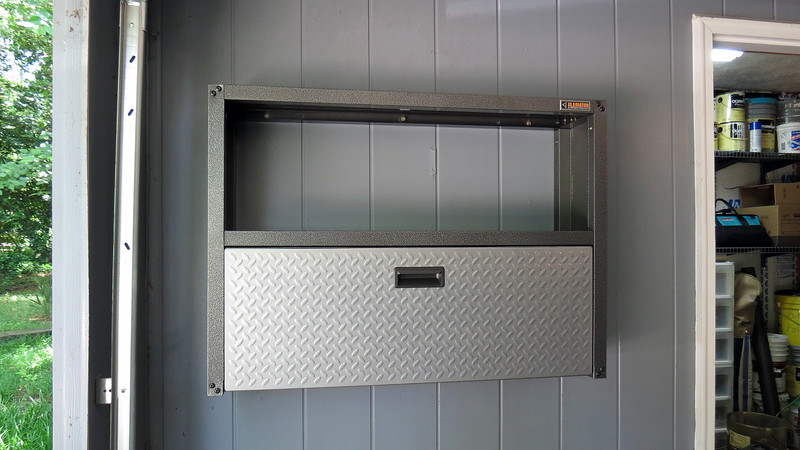 """The cabinet door is hinged at the bottom and folds downward so it can be used as a """"work station,"""" and feels quite solid.  When not in use, the door folds upward and latches in the closed position."""