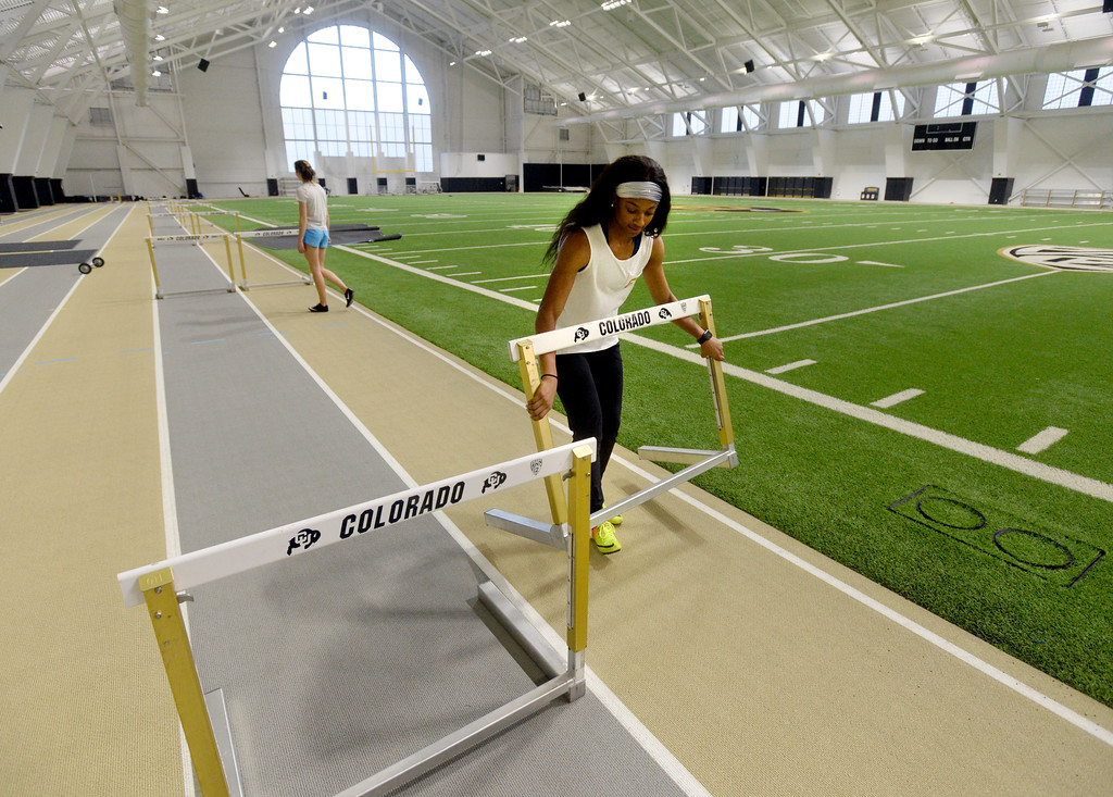 . Eriana Henderson sets up hurdles for a practice run in the IPF. The athletic facilities at the University of Colorado are nationally recognized for sustainability, such as the Indoor Practice Facility (IPF).  Cliff Grassmick  Photographer December 15, 2017