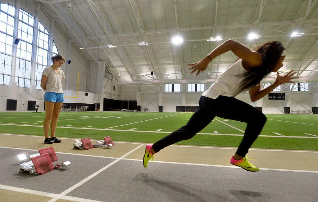. Valerie Welch , left, watches Eriana Henderson run the hurdles in the IPF on Friday. The athletic facilities at the University of Colorado are nationally recognized for sustainability, such as the Indoor Practice Facility (IPF).  Cliff Grassmick  Photographer December 15, 2017
