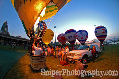 A crowd gathers around a hot air balloon during on of the balloon glows on the Great Lawn.