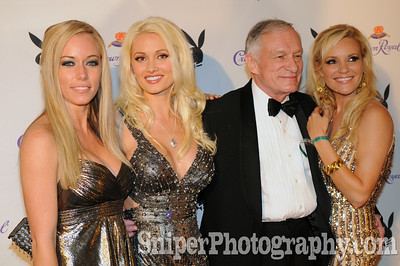 Hugh Hefner and his 3 girlfriends posing on the red carpet during the Derby Eve Crown Royal Playboy party.