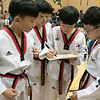 Reingold Elementary School in Fitchburg got a visit from The Korean National Taekwondo Demo Team who did some demonstration for the students on Tuesday, Oct. 8, 2019. Students from the team sign one of the boards they broke after their show for the school. SENTINEL & ENTERPRISE/JOHN LOVE