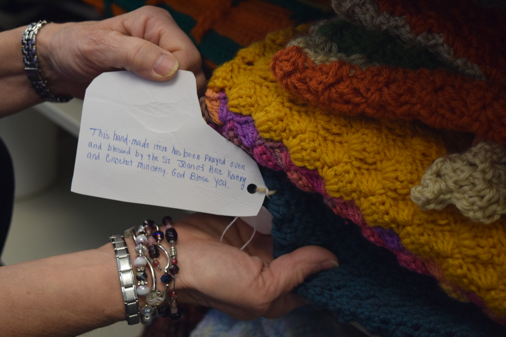. Madeline Bialecki, director of the Lake House displays a handcrafted blanket donated to the Lake House by members of the St. Joan of Arc Catholic Church crochet ministry.