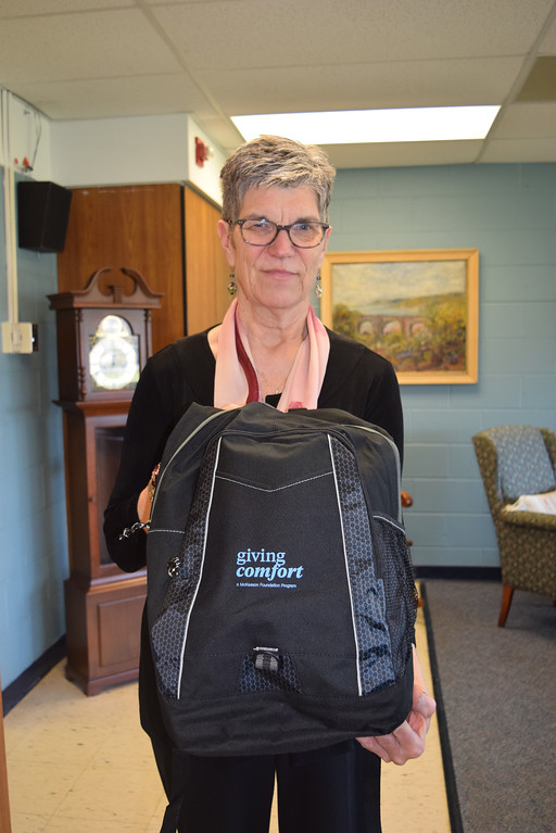 . Madeline Bialecki, director of the Lake House, holds up a backpack that is given to adults and children who attend the Lake House programs. Each backpack donated by the McKesson Foundation contains comforting items such as blanket, journal or head scarf.