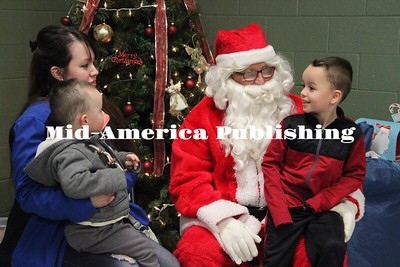 Curran McLaughlin | The Leader Caden Martinez sits on Santa's lap while Cassie Salinas holds Cade Martinez.