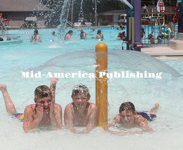 With temps in the '80s and '90s, the Garner Aquatic Center is a popular spot, lately. Zane Hawe, Brandon Roberts and Jace Hendrikson cool off under a spray feature.  Rebecca Peter|The Leader