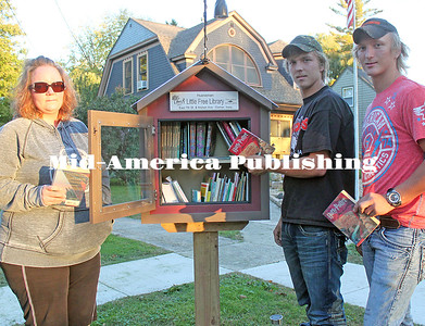 """Mollie Hueneman with sons Trevor and Jake at their """"Little Free Library"""" on East 7th St. and Maben Ave. in Garner. Leader photo by Rebecca Peter"""