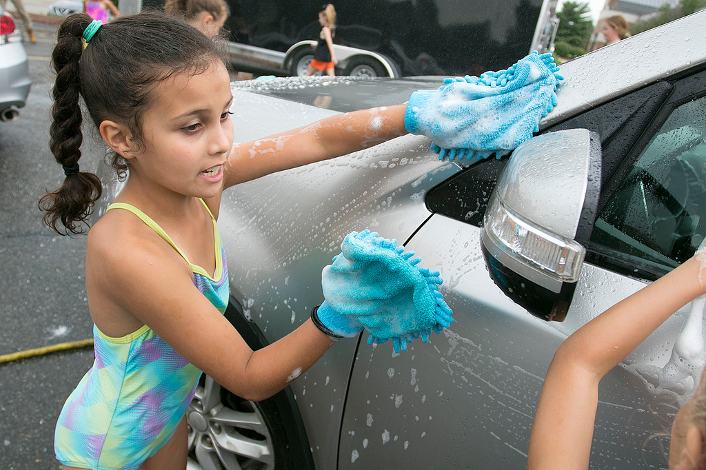 . The Lunenburg Bengals cheerleading team held a car wash funraiser in the parking lot of Central Mass Powersports for the sixth year on Saturday, August 3, 2019. They are a big sponsor of the team. The team is made up of kids from kindergarten to eighth grade. Elisia Tau Golden, 8, with two hand scrubbers helps makes sure this car was clean during the fundraiser. SENTINEL & ENTERPRISE/JOHN LOVE