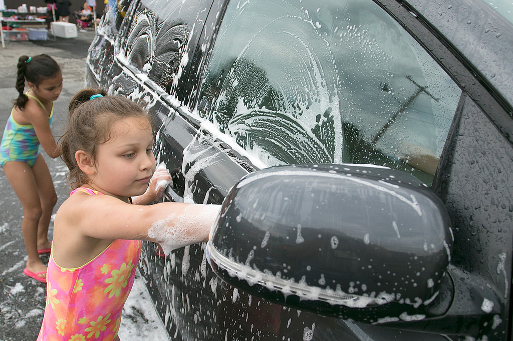. The Lunenburg Bengals cheerleading team held a car wash funraiser in the parking lot of Central Mass Powersports for the sixth year on Saturday, August 3, 2019. They are a big sponsor of the team. The team is made up of kids from kindergarten to eighth grade. Ella Tau Gooden, 7, washes one of the cars at the fundraiser. SENTINEL & ENTERPRISE/JOHN LOVE