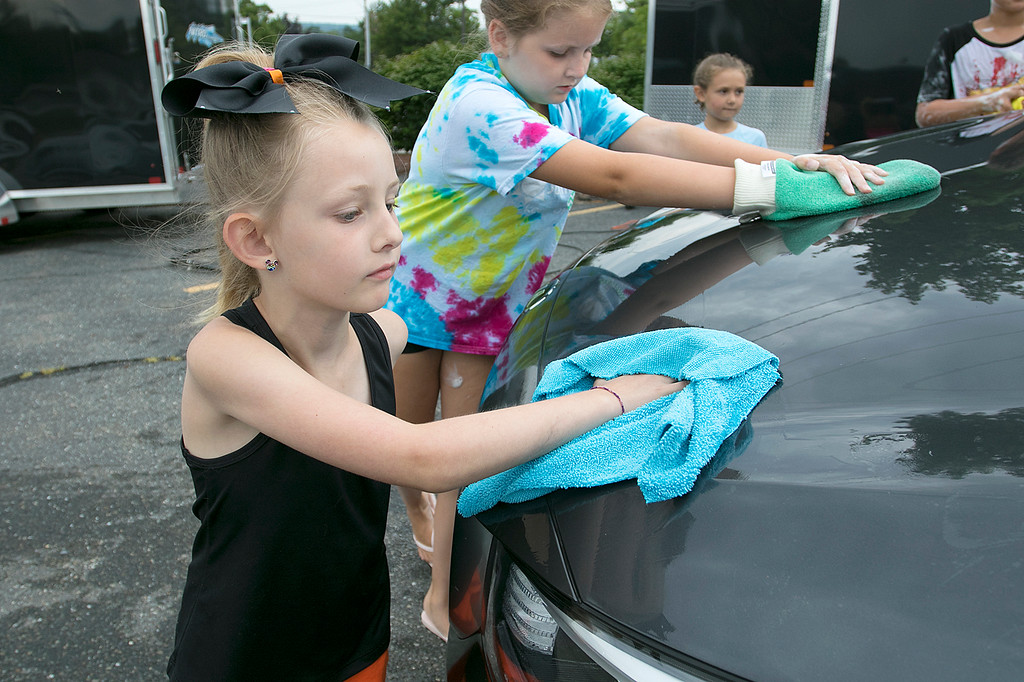. The Lunenburg Bengals cheerleading team held a car wash funraiser in the parking lot of Central Mass Powersports for the sixth year on Saturday, August 3, 2019. They are a big sponsor of the team. The team is made up of kids from kindergarten to eighth grade. Rylee LeClair, 7, helps dry one of the cars they washed at the fundraiser. SENTINEL & ENTERPRISE/JOHN LOVE