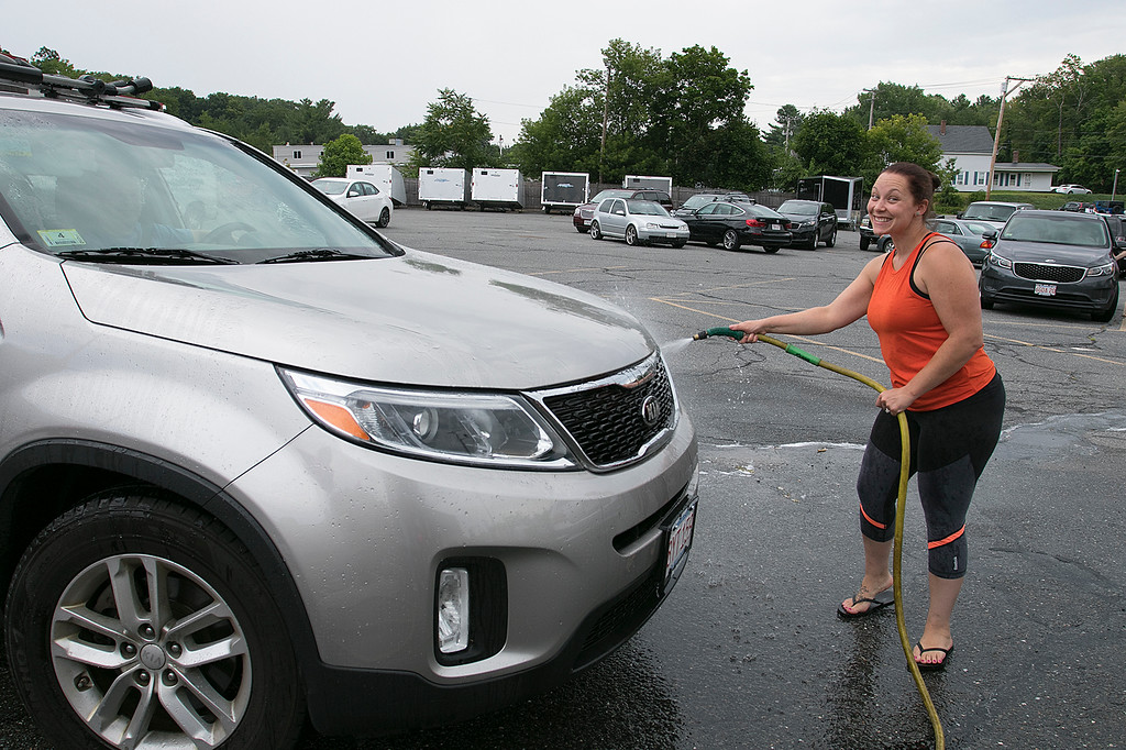 . The Lunenburg Bengals cheerleading team held a car wash funraiser in the parking lot of Central Mass Powersports for the sixth year on Saturday, August 3, 2019. They are a big sponsor of the team. The team is made up of kids from kindergarten to eighth grade. Team Coach Nichole Bishop wets down one of the cars at the fundraiser. SENTINEL & ENTERPRISE/JOHN LOVE