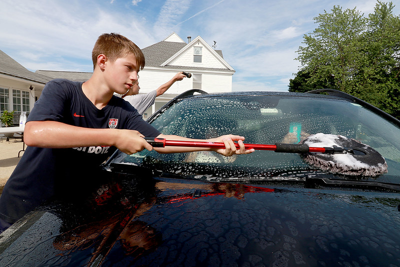The Lunenburg Skate Park project held a funraising car wash on Friday night out in front of the Eagle House Senior Center. They presold about 70 tickets to the funraiser. Chris Roy, 13, one of the helpers at the event washes the windshield on one of the cars that came through. SENTINEL & ENTERPRISE/JOHN LOVE