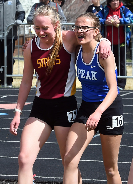 . Emma Schaefer, left, of Shining Mountain, and Jenna Howard, of Peak to Peak, support each other after running the 1600 meters during the Lyons Invitational track meet on Saturday. For more photos, go to BoCoPreps.com. Cliff Grassmick  Photographer  March 31, 2018