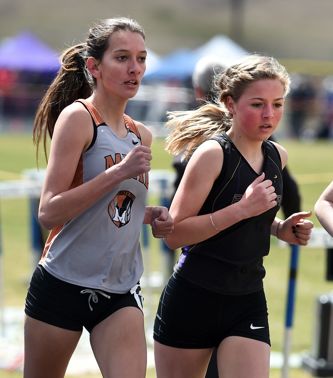 . Kaitlyn Salazar, left, of Mead, and Miria Moore, of Boulder, run in the first heat of the 1600 meters during the Lyons Invitational track meet on Saturday. For more photos, go to BoCoPreps.com. Cliff Grassmick  Photographer  March 31, 2018