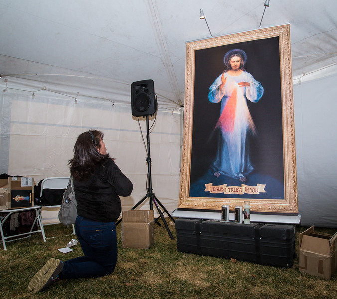 A pilgrim kneels in the Divine Mercy For America tent on the grounds of the National Shrine during the 2012 Mercy Sunday festivities.  April 7, 2013