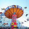 Adults and kids scream as the Navy Pier Wave Swinger Ride spins them into the air.