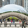 "Tourist talking, walking and taking cell phone photos of themselves reflected in ""The Bean"" in Chicago, Illinois, USA"