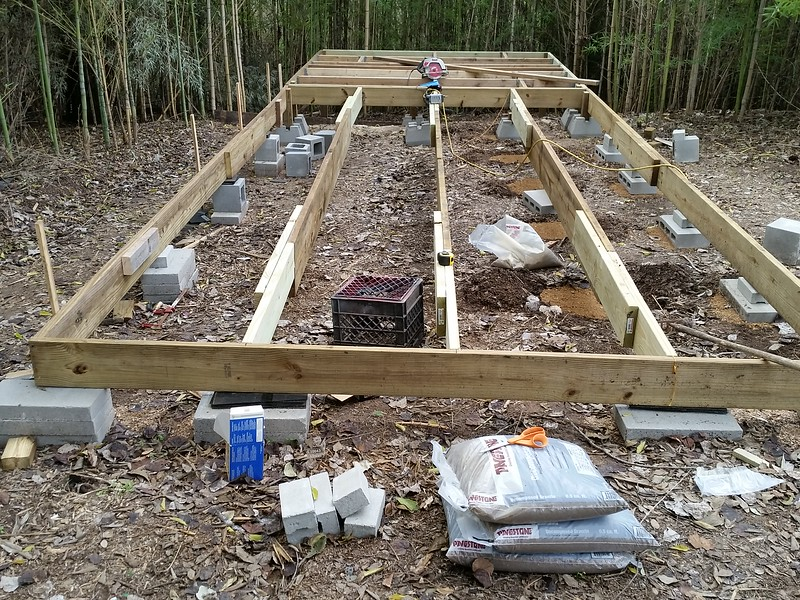 """Main beams in place but not """"supported"""" in the middle like the one on the far right and the one on the far left. Will prepare each location for supports like the second from the right then measure the distance to the rock bed so I won't have to guess at which and how many cinder blocks of what size and thickness will be needed to finish up."""