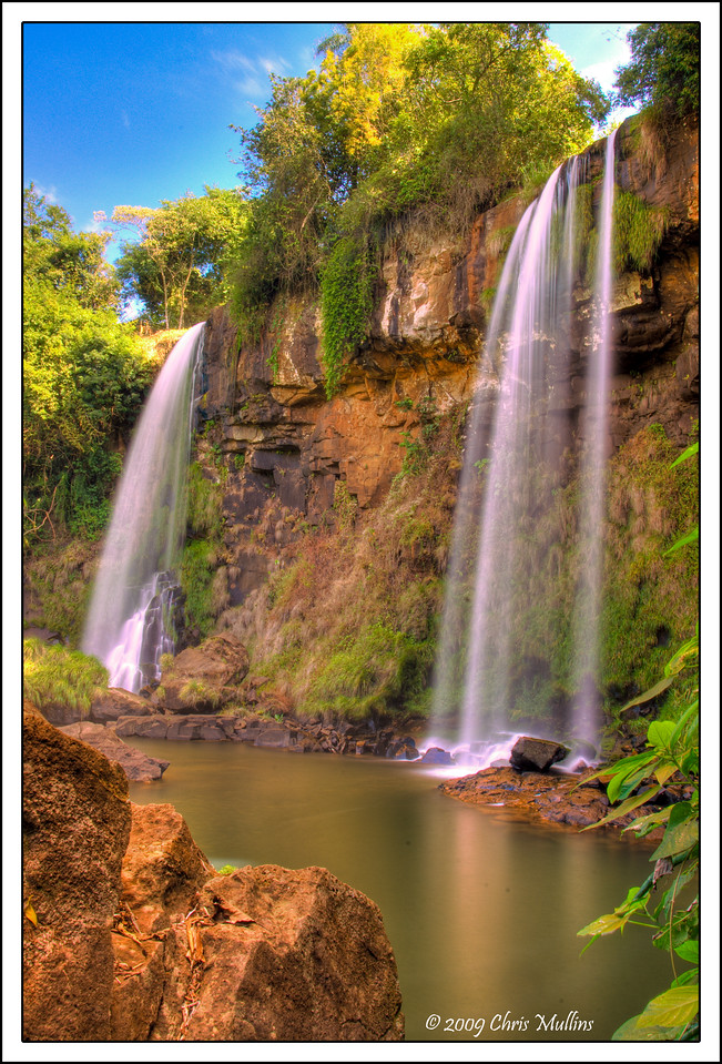 Two small waterfalls at tumble into a river at Puerto Iguazú National Park in Argentina. This area is all part of the Iguazu Falls zone.