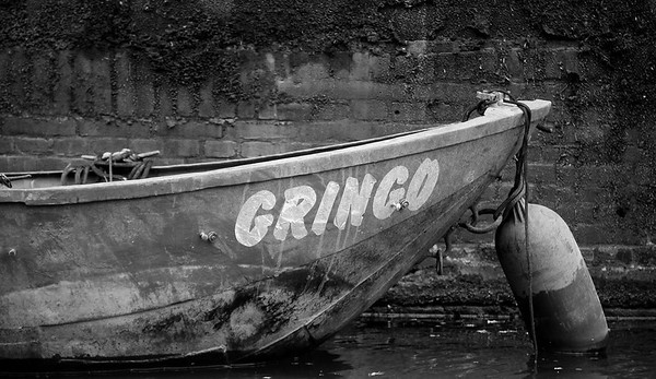 Gray scale interpretation of a small fishing boat docked in Amsterdam.