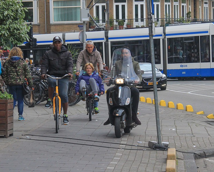On this expanded sidewalk in Amsterdam motorcycles race by bikes and pedestrians at traffic speeds with no intention of stopping.