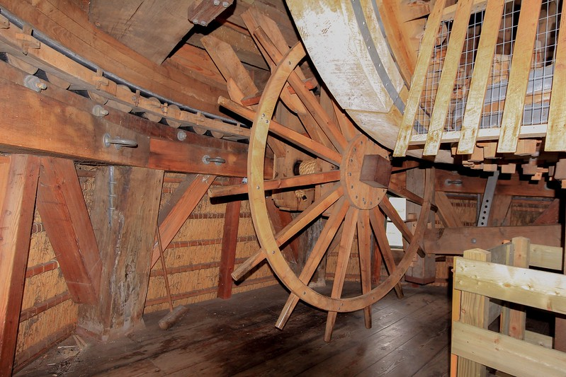 """The spoked wheel is the """"winder"""", used to manually turn the cap into the wind. Turning the wheel 1/8th of a full revolution rotates the cap (which weighs 20 tons) only about an inch. On days with variable winds this is a full time job. Notice the outer wall at the floor is clearly an octagonal shape, yet at the rollers the room has transitioned into a perfect circle. Tricky woodwork."""