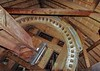 The semi-circular wooden piece on the outside of the tooth ring is the brake arm that is employed (using weights) to stop the windshaft/sails from turning for sail adjustments or for the gears to be engaged or disengaged. This photo was captured about 1/2 way up the steps while looking straight down. When the brake engages it takes a while for the windshaft to slide to a stop.