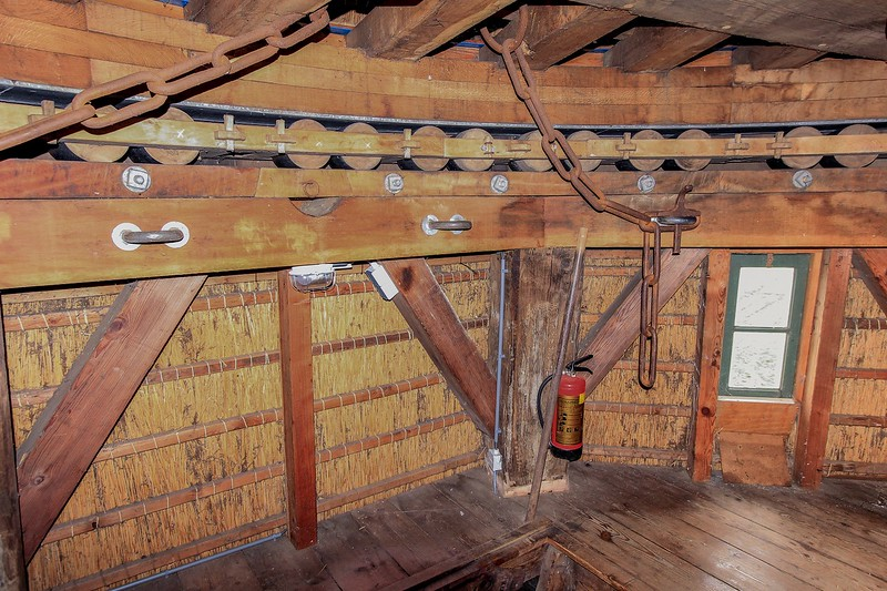 """Here we are inside the windmill at the top under the """"cap"""", which is the entire upper part of the structure. It supports the sails and blade assembly and is designed to rotate so the sails can be faced directly into the wind. The entire cap assembly spins on many pairs of tough little wooden rollers, shown here. The chains hold the cap in place."""