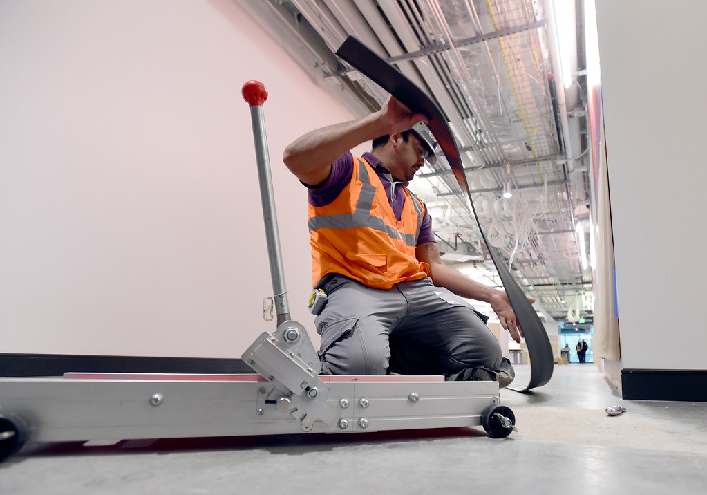 . Mario Ramirez, with BLT Flooring, applies cove base to the walls during a tour of the new Google campus on Pearl Street in Boulder. Jeremy Papasso/ Staff Photographer 10/02/2017