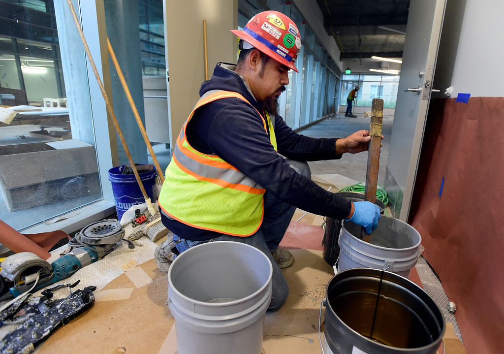 . Adrian Perez, with Omnitech Industries Inc., mixes primer to be applied to the floor in the Bill Davis Bike and Ski Shop inside the new Google campus on Pearl Street in Boulder. Jeremy Papasso/ Staff Photographer 10/02/2017