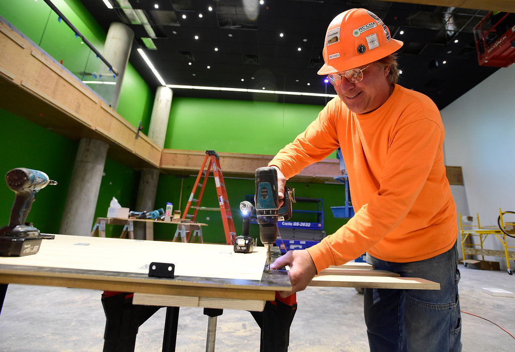 . Michael Lorenzen, with Woodcraft Unlimited, drills holes in a wood panel to be installed on the wall of the Tech Talk room during a tour of the new Google campus on Pearl Street in Boulder. Jeremy Papasso/ Staff Photographer 10/02/2017