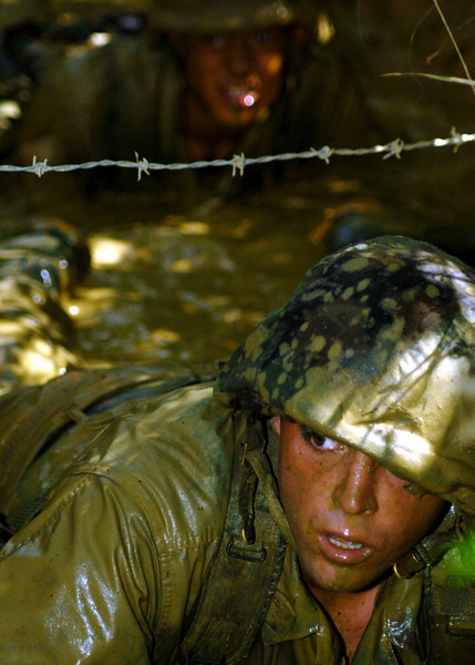 050817-N-1261P-198<br /> Okinawa, Japan (Aug. 17, 2005) - U.S. Navy Utilitiesman 3rd Class Justin T. Mackubbin low-crawls through mud-filled trenches as part of an obstacle course at the Jungle Warfare Training Center (JWTC), located in the Northern Training Area on the island of Okinawa. Petty Officer Hawkins is assigned to Naval Mobile Construction Unit Seven Four (NMCB-74). U.S. Navy photo by Photographer's Mate 2nd Class Eric S. Powell (RELEASED)