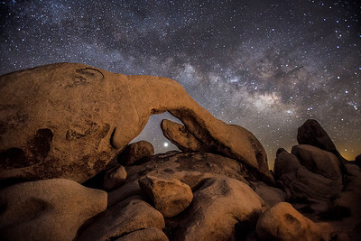 The Milky Way and Venus rise behind Arch Rock in Joshua Tree National Park.
