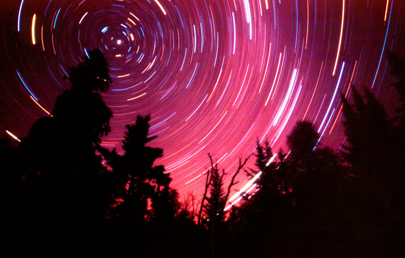 Northwoods Star Trails. Photographed late in July on the edge of the Boundary Water Canoe Area Wilderness (BWCA). I have spent several years photographing the night sky and this is one of my better attempts. I wish I could have left the shutter open a little bit longer than this1 hour exposure. Photographed with a Nikon FG FILM camera and Fuji Velvia slide film.  Prints of the image are available up to 24x36 ins or larger, if you are willing to pay a little more! VIVA LA FILM!!!!!!!!!!!!!!!  -Michael Maltese