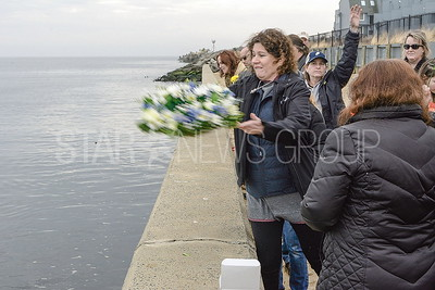 dennis' aunt teresa throwing the wreath into the inlet