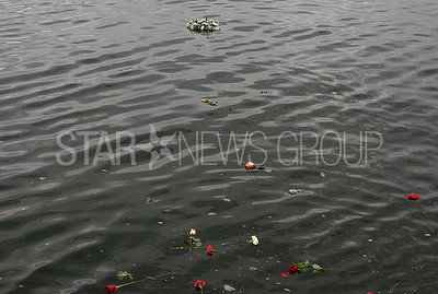 mourners threw a wreath and flowers into the inlet