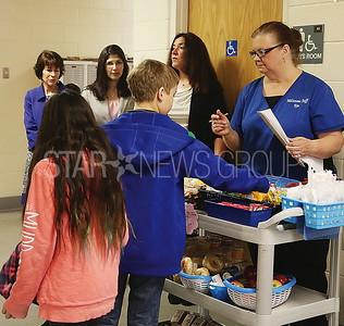 BRICK Midstream Elem. Breakfast/ Staff member Kim Petillou brings the breakfast tray to each classroom
