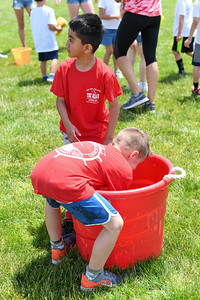 First graders Dylan (back) and Brandon (front) fill their sponges with water during the Sponge Relay at Antrim Elementary's Field Day on June 6, 2019. [ALYSSA RASP | THE OCEAN STAR]