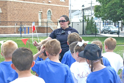Officer Taylar Verrier, the school resource office, gathering the children. The 2019 Field Day at Lavallette Elementary in Lavallette, NJ on 6/6/19. [DANIELLA HEMINGHAUS   THE OCEAN STAR]